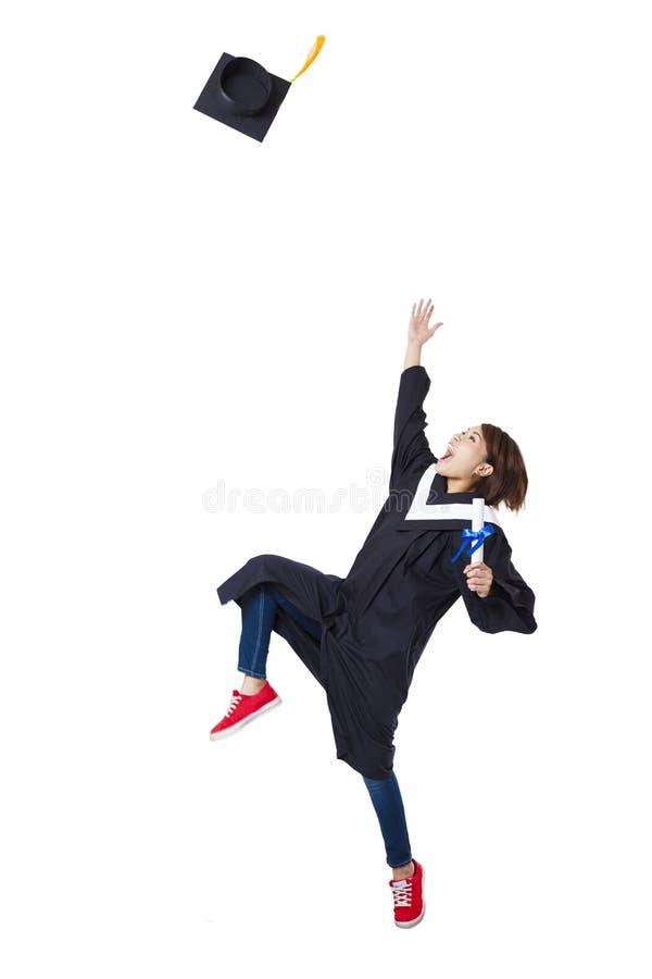 Gelukkige student in het gediplomeerde robe dansen stock foto