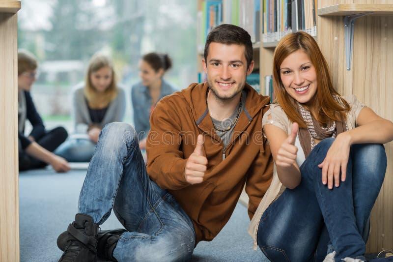 Gelukkige studenten die duim in bibliotheek tonen royalty-vrije stock fotografie
