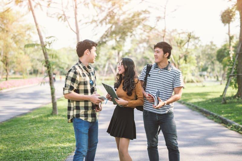 Gelukkige studenten die en elkaar in een campus lopen spreken bij park met een warm licht royalty-vrije stock foto