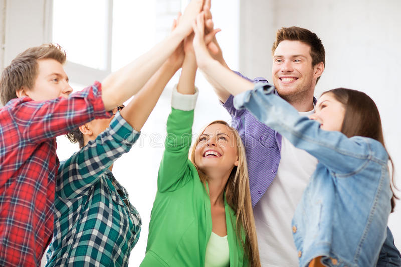 Gelukkige studenten die hoogte vijf geven op school stock fotografie