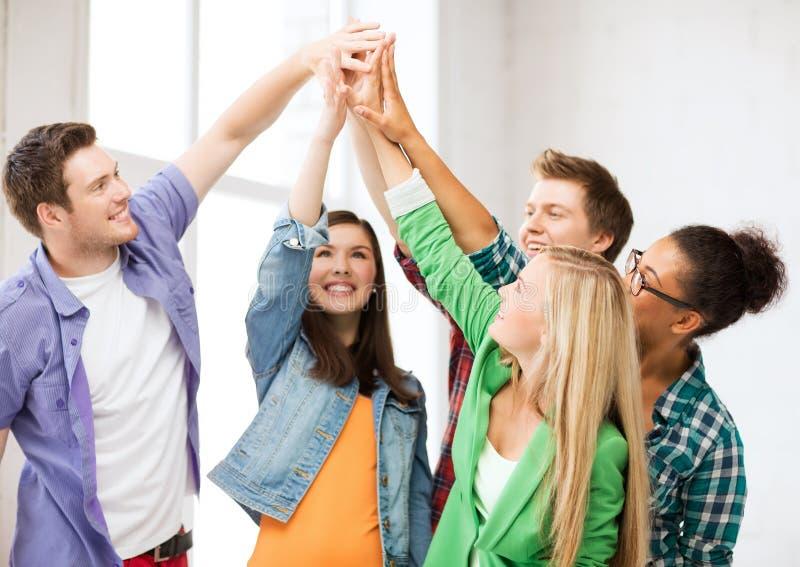 Gelukkige studenten die hoogte vijf geven op school stock afbeeldingen