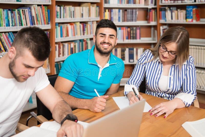 Gelukkige Studenten die met Laptop in Bibliotheek werken royalty-vrije stock fotografie