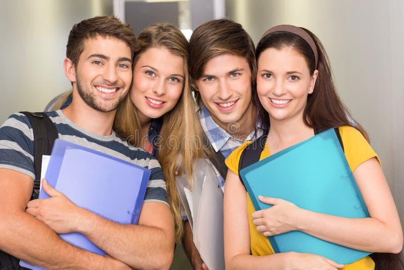 Gelukkige studenten die omslagen houden bij universiteitsgang stock afbeelding