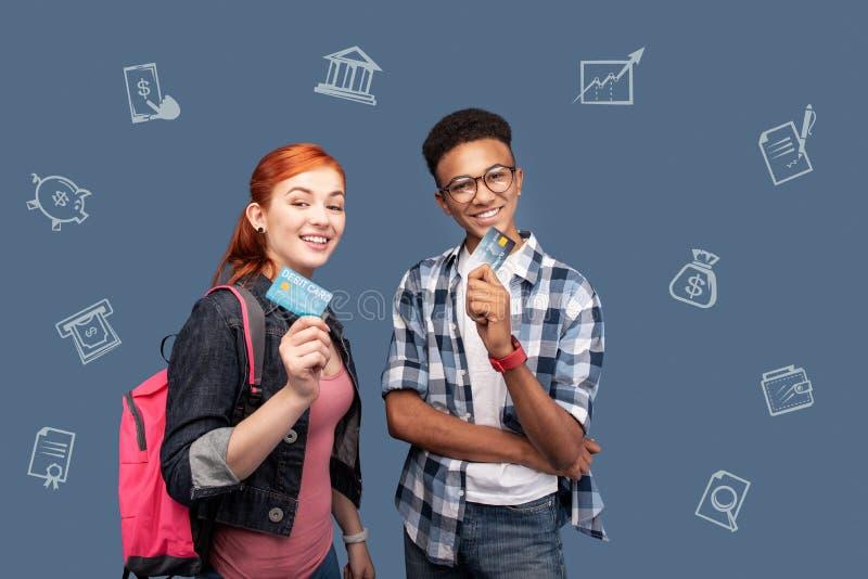 Gelukkige studenten die terwijl het hebben van hun eerste creditcards glimlachen stock afbeelding