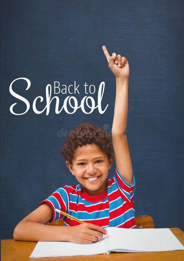 Gelukkige studentenjongen die bij lijst hand opheffen tegen blauw bord met terug naar schooltekst stock fotografie
