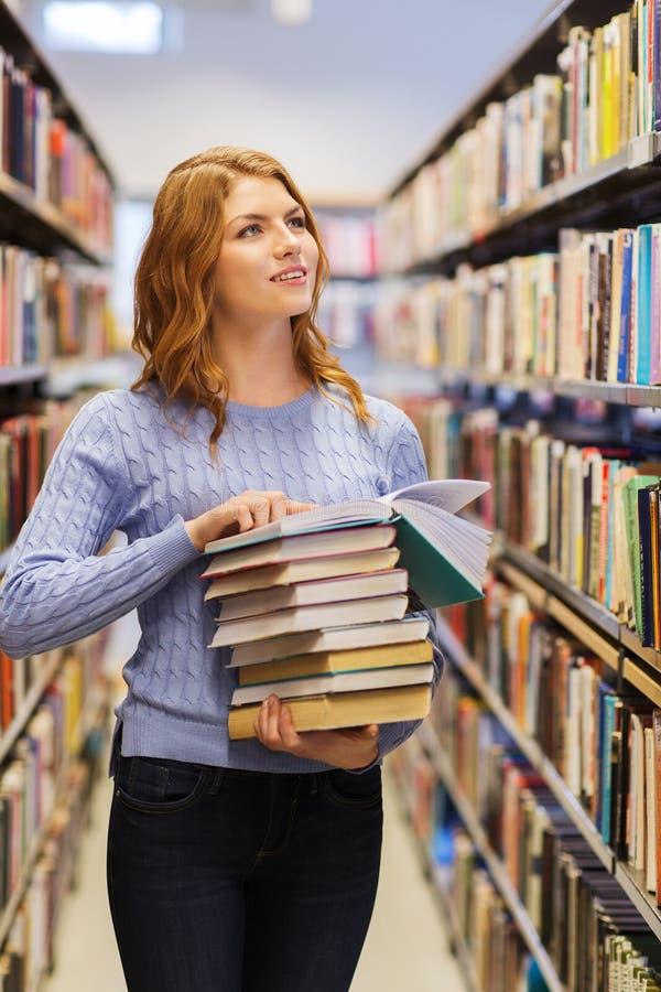 Gelukkige studentenmeisje of vrouw met boeken in bibliotheek stock foto's