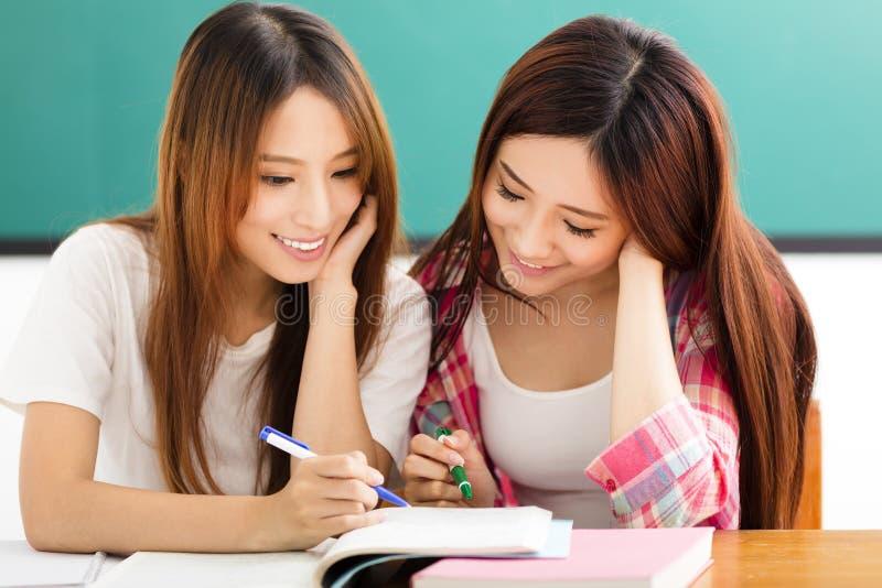 Gelukkige studentenmeisjes die op de boeken in klaslokaal letten stock foto