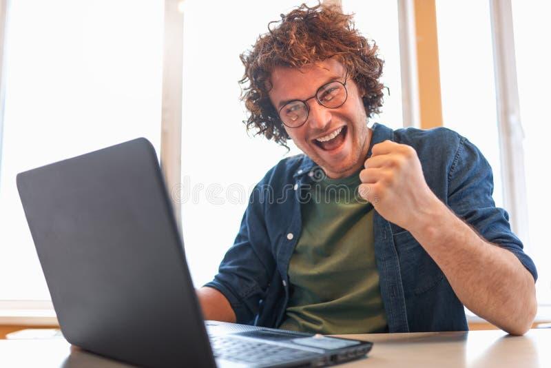 Gelukkige succesvolle jonge zakenman die laptop met behulp van bij zijn bureau die winnaargebaar maken royalty-vrije stock foto's