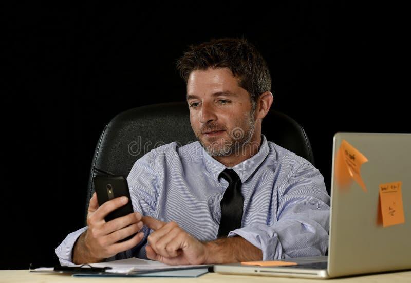 Gelukkige succesvolle zakenman die bij het bureau van de bureaucomputer met mobiele telefoon glimlachen stock foto