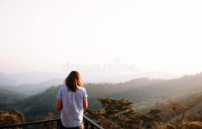 Gelukkige succesvrouw bij zonsondergang of zonsopgang die zich bij berg bevinden stock fotografie