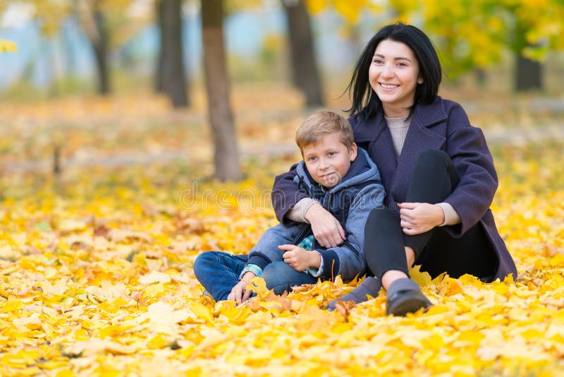 Gelukkige, tevreden moeder en zoonszitting in park royalty-vrije stock afbeelding
