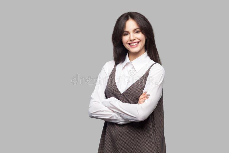 Gelukkige tevreden mooie jonge vrouw in wit overhemd en bruine schort met make-up en donkerbruin haar die zich met gekruiste wape stock foto's