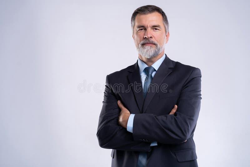 Gelukkige tevreden rijpe zakenman die die camera bekijken op witte achtergrond wordt geïsoleerd royalty-vrije stock afbeelding