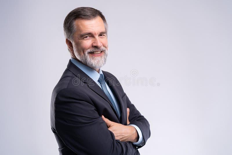 Gelukkige tevreden rijpe zakenman die die camera bekijken op witte achtergrond wordt geïsoleerd royalty-vrije stock foto