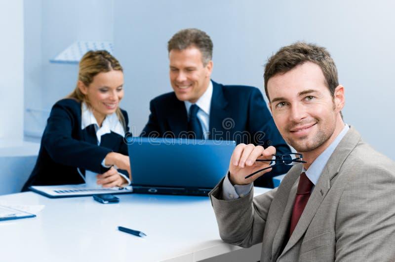 Gelukkige tevreden zakenman met collega's stock afbeeldingen