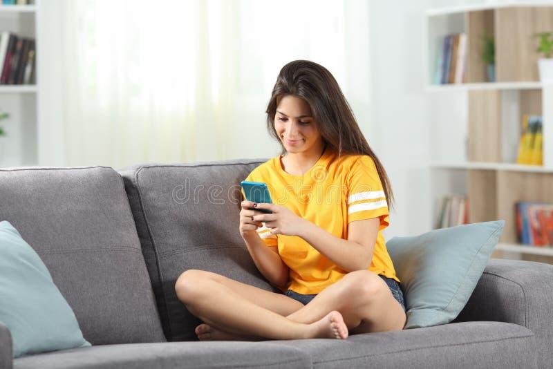 Gelukkige tiener die een mobiele telefoon op een laag met behulp van stock foto