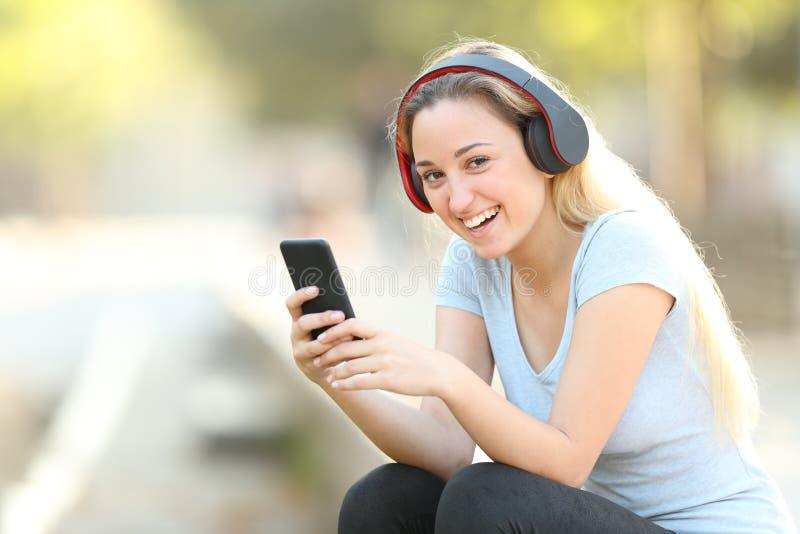 Gelukkige tiener die een smartphone houden bekijkend u stock fotografie