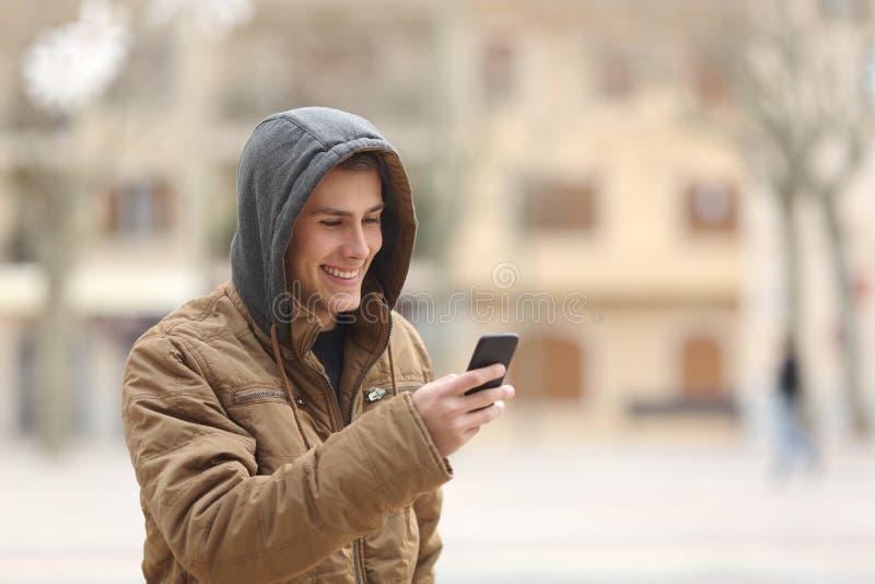 Gelukkige tiener die en een slimme telefoon lopen met behulp van royalty-vrije stock afbeeldingen