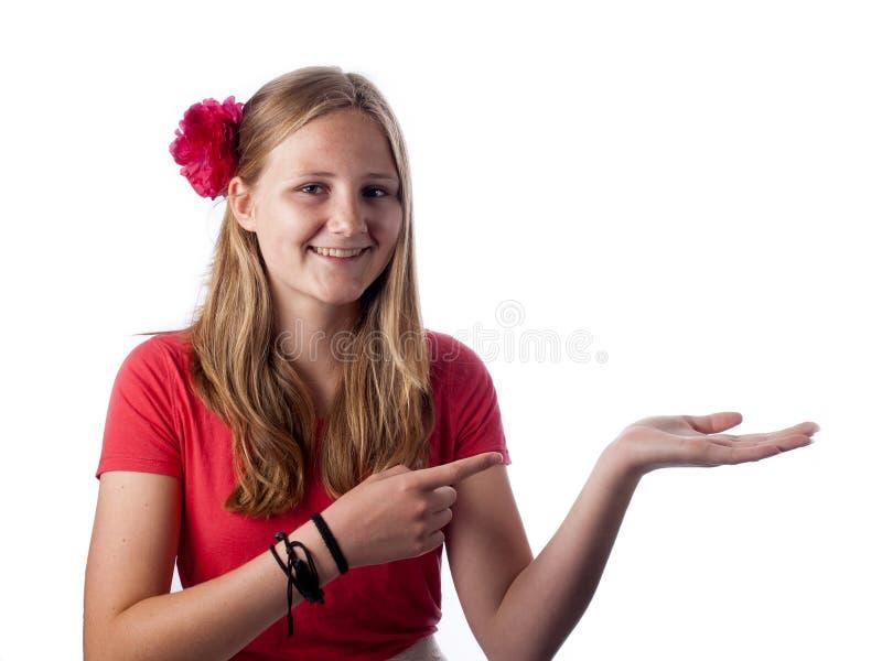 Gelukkige tiener die iets op de palm van haar hand tonen stock afbeelding