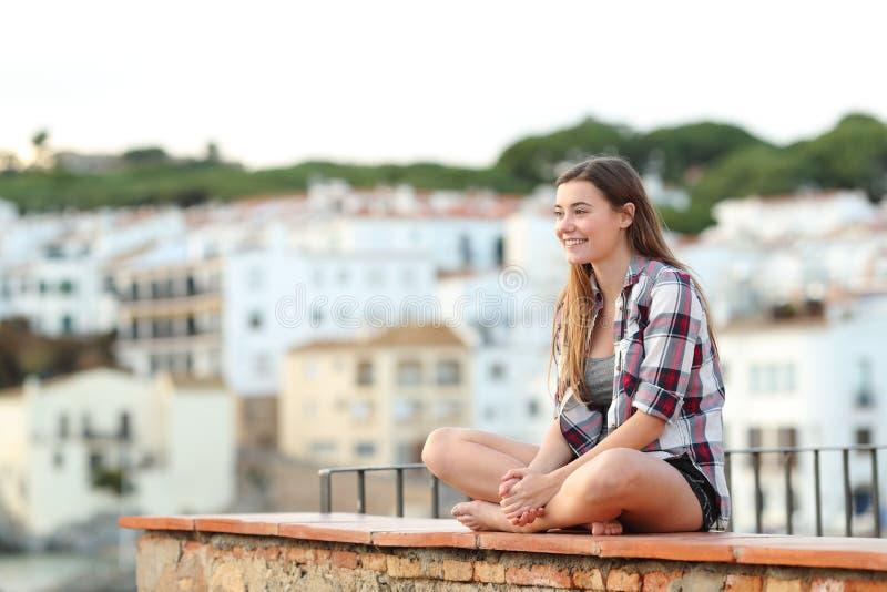 Gelukkige tiener die meningen overwegen die op een richel zitten royalty-vrije stock afbeelding