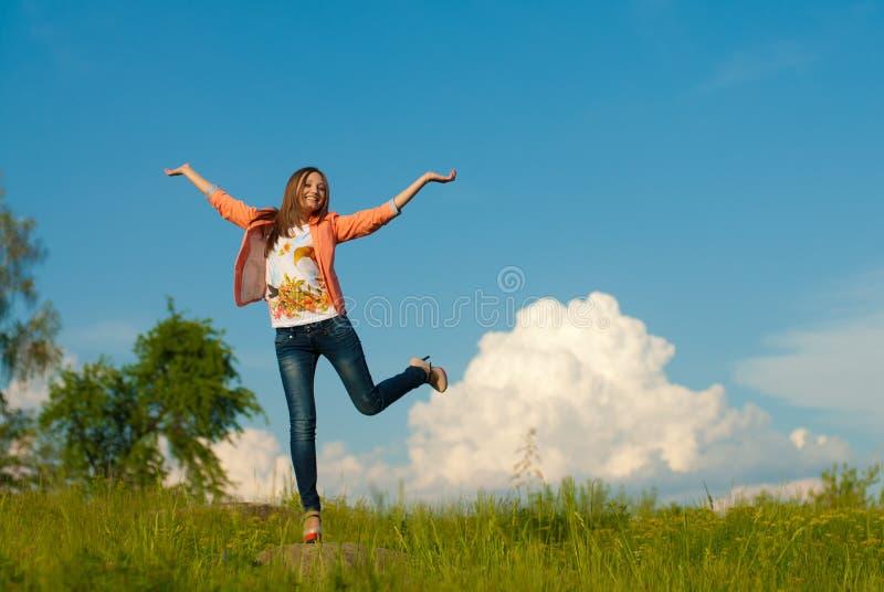 Gelukkige tiener die op de de zomer in openlucht achtergrond springen stock foto