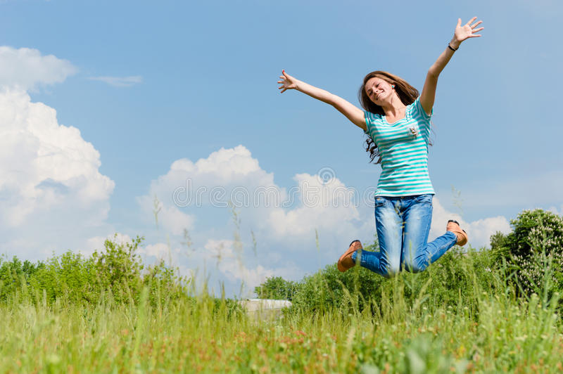 Gelukkige tiener die op de de zomer in openlucht achtergrond springen stock fotografie