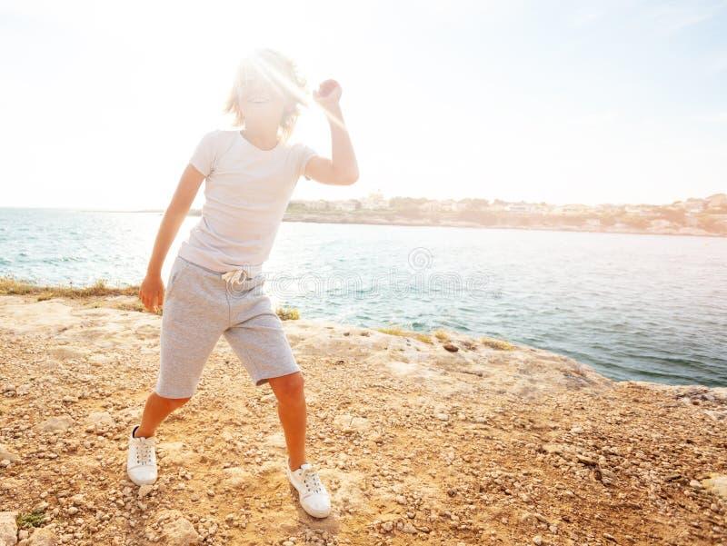 Gelukkige tiener die op het strand in de zomer dansen royalty-vrije stock fotografie