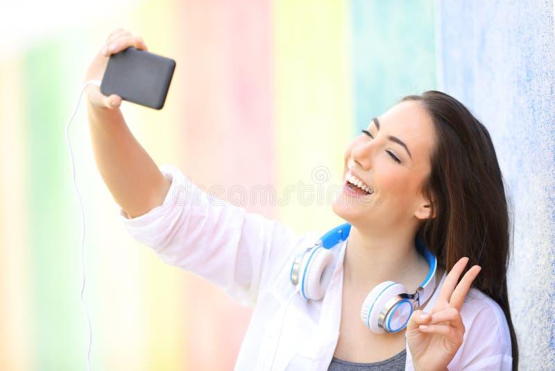 Gelukkige tiener die selfies in een kleurrijke straat nemen stock fotografie