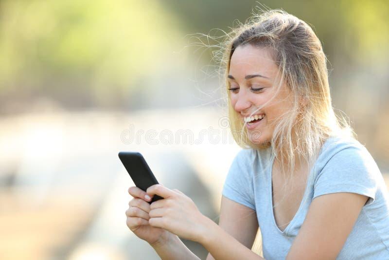 Gelukkige tiener die telefooninhoud in een park controleert stock fotografie