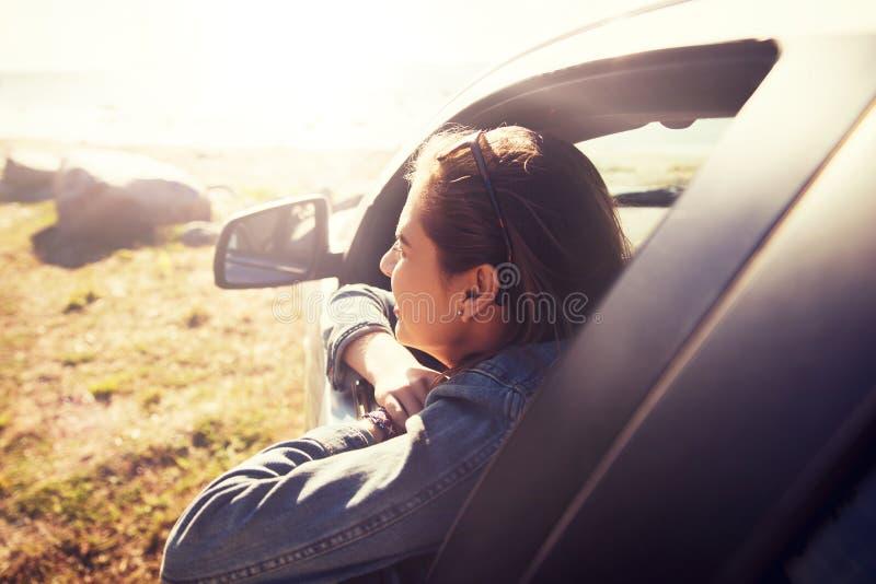 Gelukkige tiener of jonge vrouw in auto stock afbeeldingen