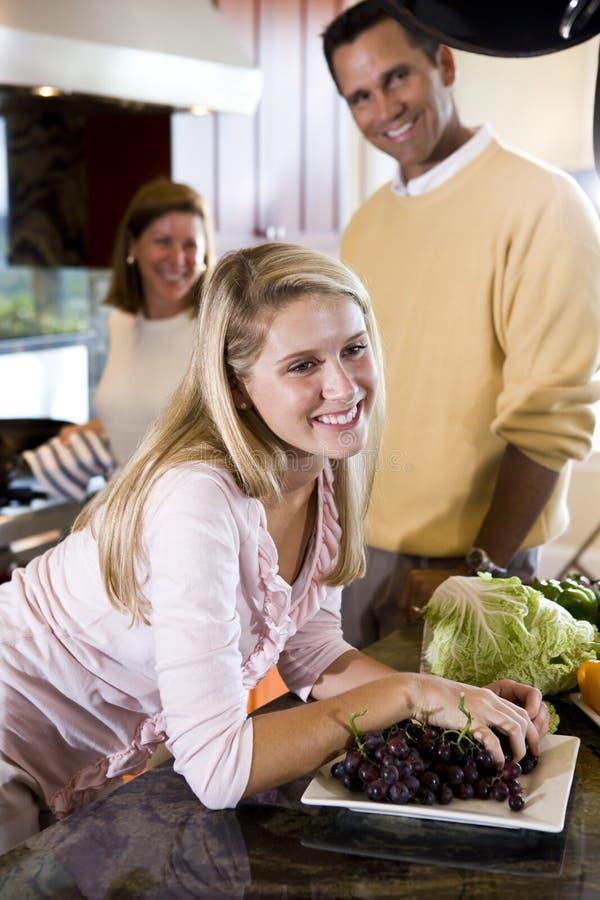 Gelukkige tiener in keuken met ouders stock fotografie