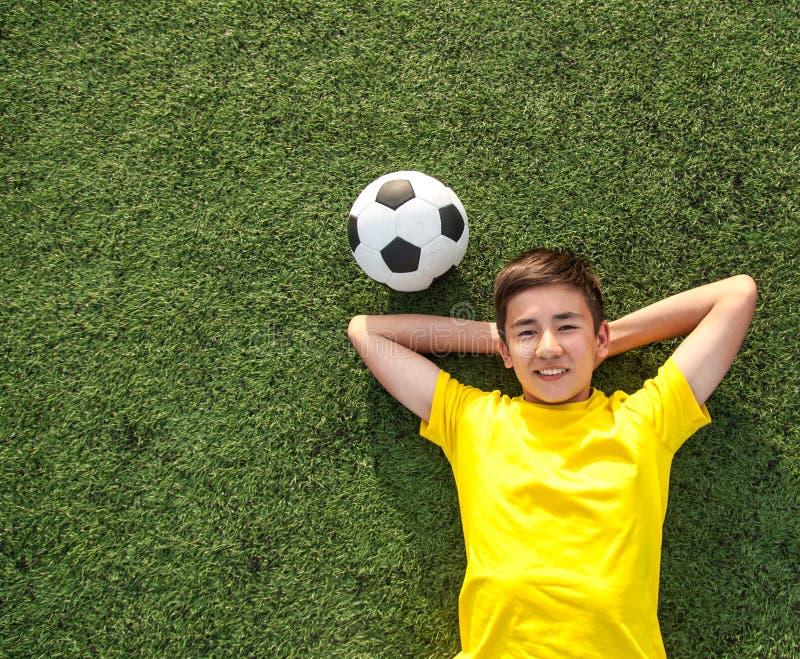 Gelukkige tiener met een voetbalbal die op het groene gazon liggen royalty-vrije stock fotografie