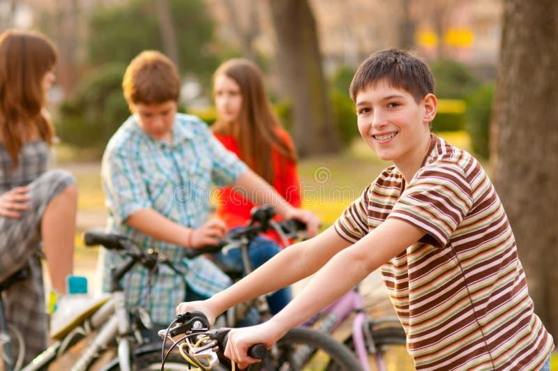 Gelukkige tiener op fiets met vrienden stock afbeelding