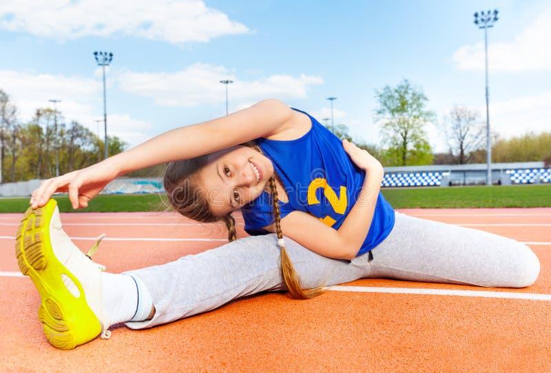 Gelukkige tiener yoga maken die buiten zich uitrekt stock fotografie