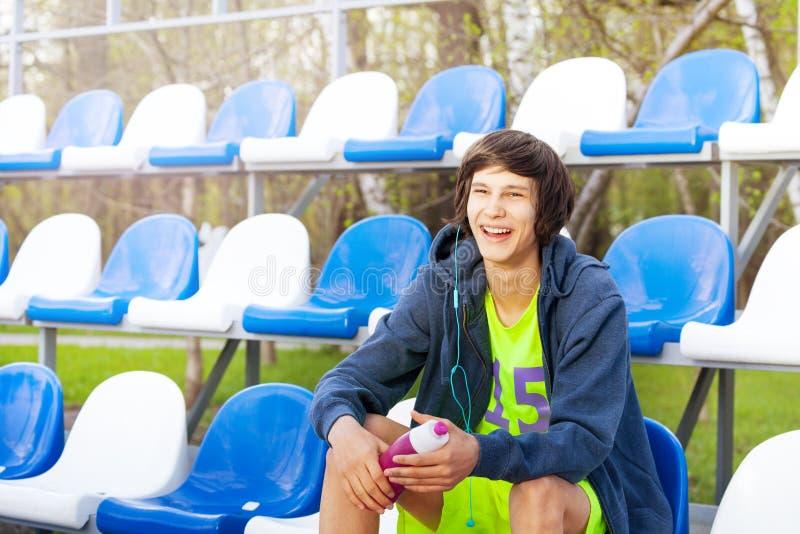 Gelukkige tieneratleet die rust na training hebben stock foto's