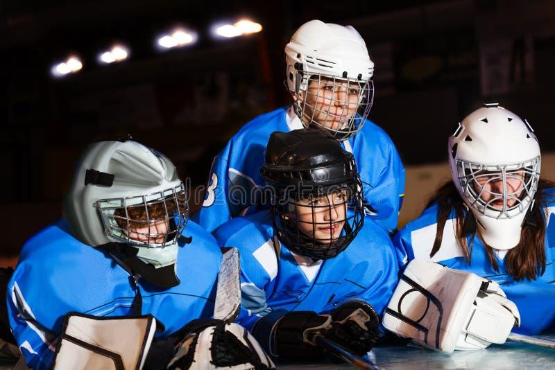 Gelukkige tienerhockeyspelers die op ijsbaan leggen royalty-vrije stock afbeeldingen