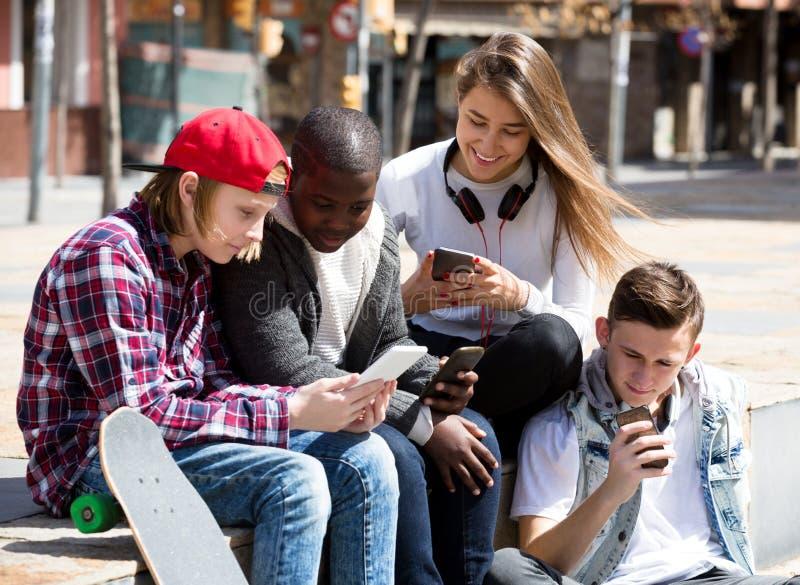 Gelukkige tienerjaren die op smarthphones spelen royalty-vrije stock foto's