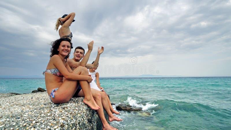 Gelukkige tienerjaren die op strandpijler zitten die pret blazende kussen hebben en handen golven royalty-vrije stock foto's