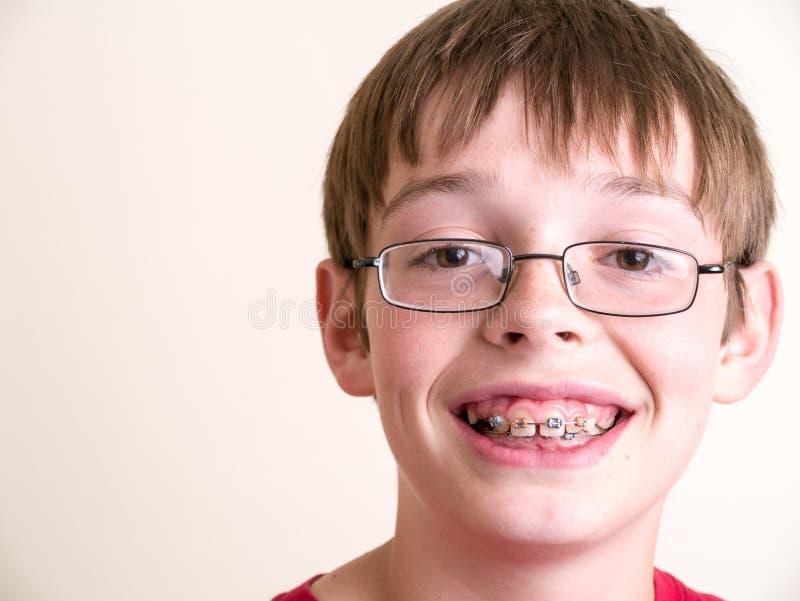 Gelukkige tienerjongen met steunen het glimlachen stock foto
