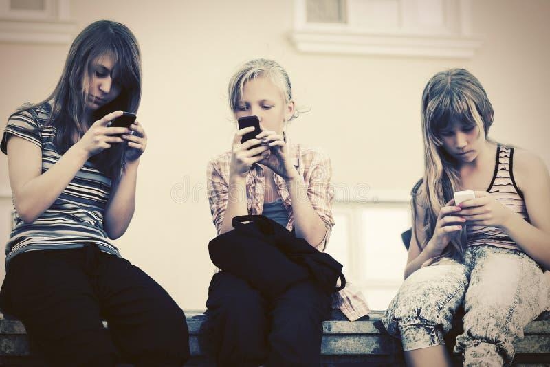 Gelukkige tienermeisjes die smartphones met behulp van tegen een schoolgebouw stock afbeeldingen