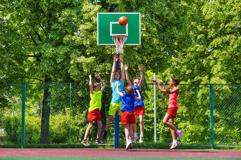 Gelukkige tieners die basketbal op speelplaats spelen royalty-vrije stock foto's