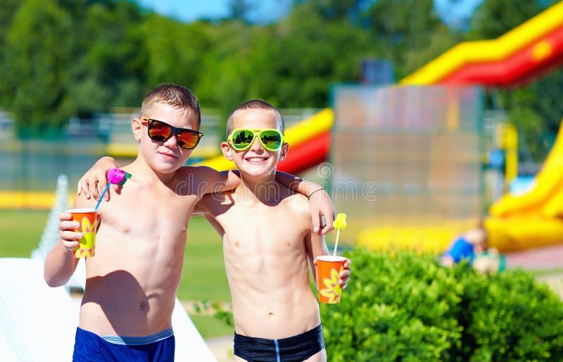 Gelukkige tieners die duimen in waterpark tonen royalty-vrije stock foto