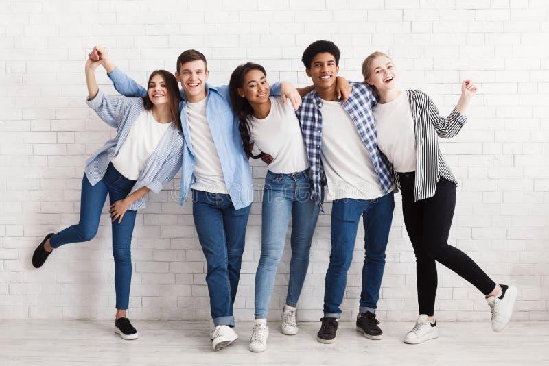 Gelukkige tieners die pret hebben en over witte muur stellen stock afbeelding