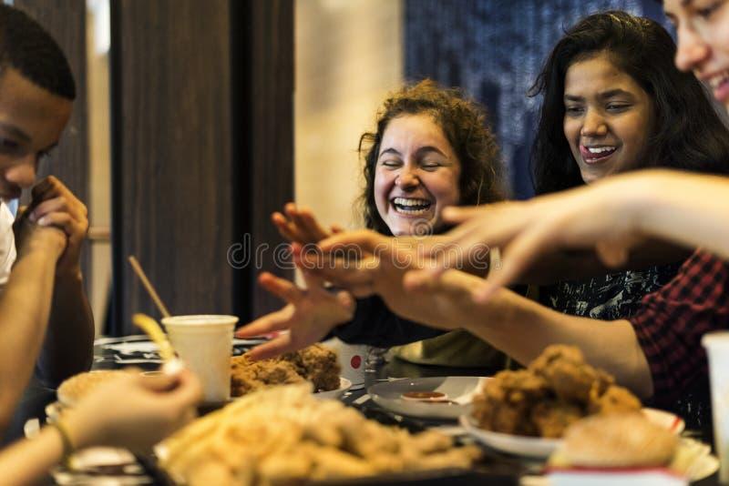 Gelukkige tieners die samen de zwaarlijvigheid van de snel voedselongezonde kost en ongezond maaltijdconcept eten stock afbeelding