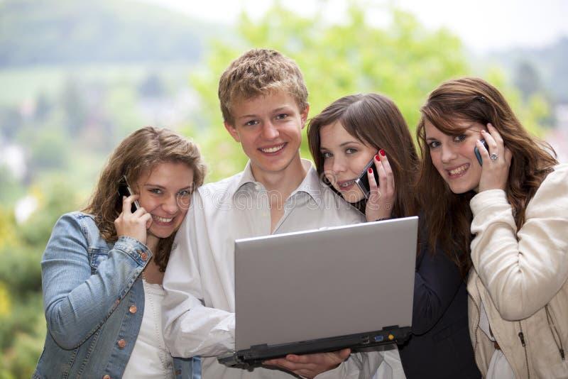 Gelukkige tieners met cellphones en laptop stock afbeelding