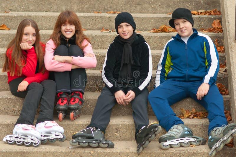 Gelukkige tieners in rolschaatsen openlucht zitten royalty-vrije stock fotografie