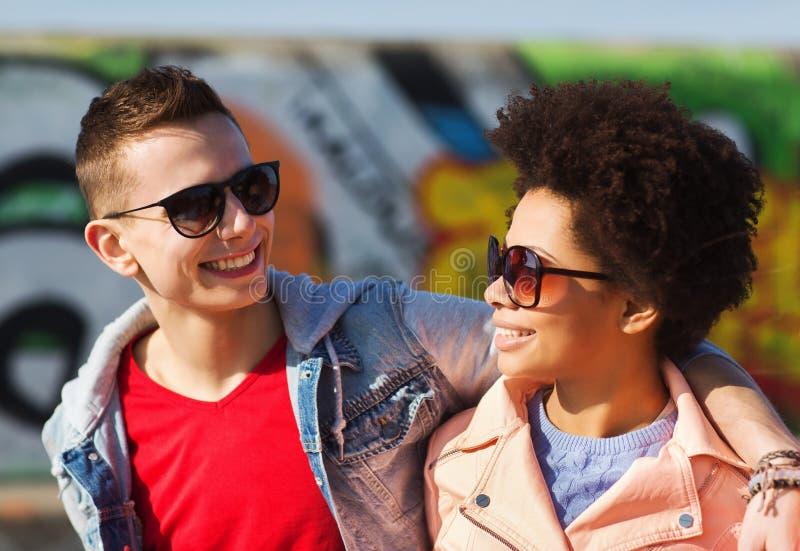 Gelukkige tienervrienden die in schaduwen in openlucht koesteren stock foto