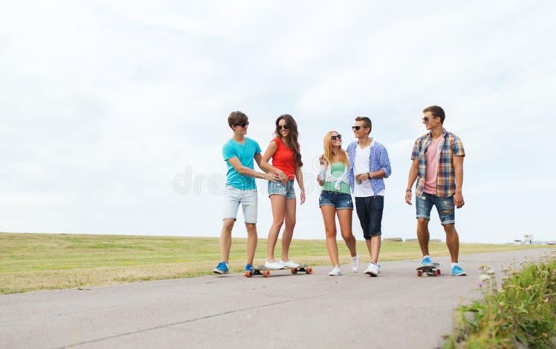 Gelukkige tienervrienden met longboards in openlucht royalty-vrije stock afbeelding