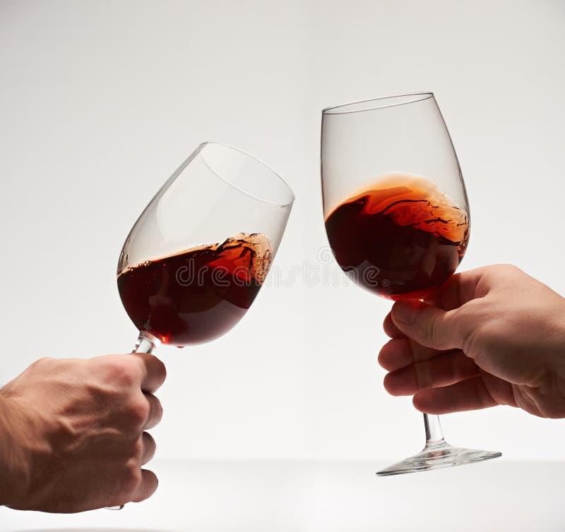 Gelukkige toejuichingen met twee rode wijnglazen stock afbeeldingen