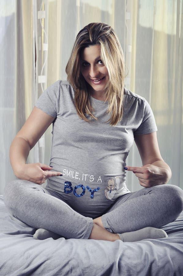 Gelukkige toekomstige mama die teken op haar zwangere buik tonen royalty-vrije stock foto's